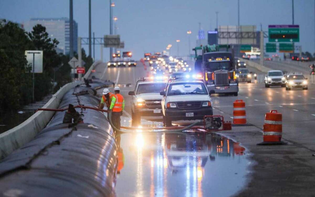 Texas Department of Transportation workers construct a temporary dam on Interstate 10 to stop water from the Addicks Reservoir from moving across the highway on Aug. 30.