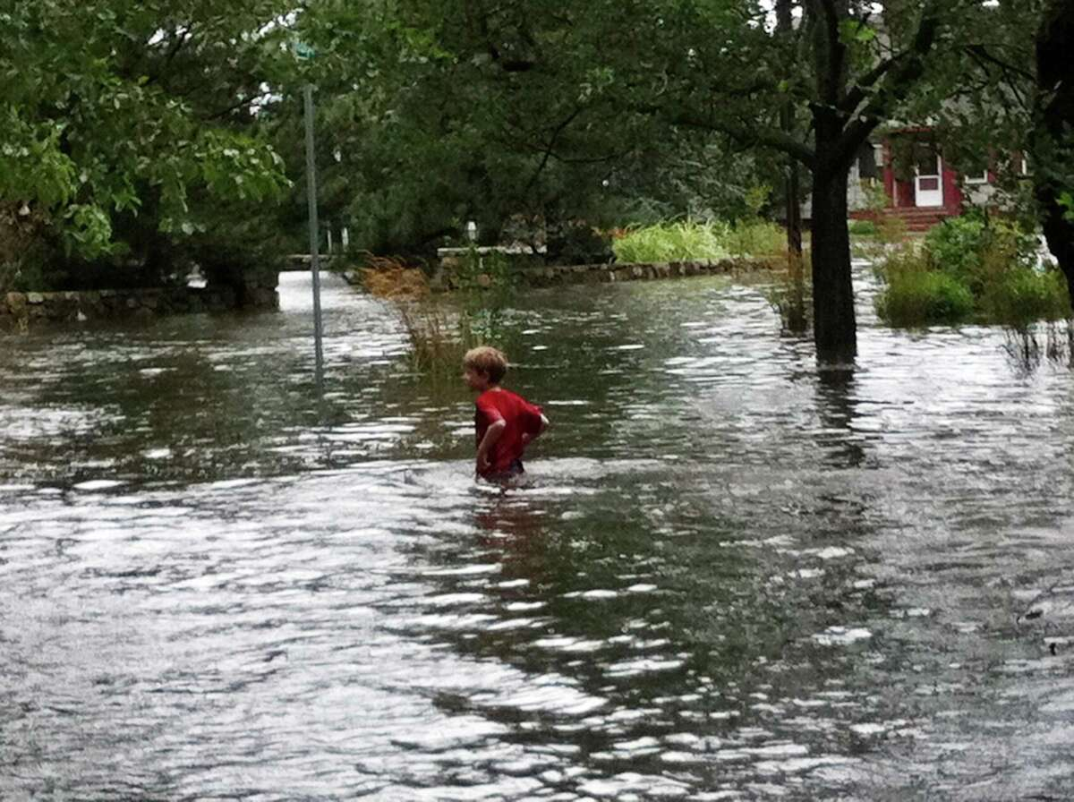 Tomek Zaleski wades along Downs Avenue as the tide comes in helped by Hurricane Irene in Stamford, Conn., August 28, 2011.