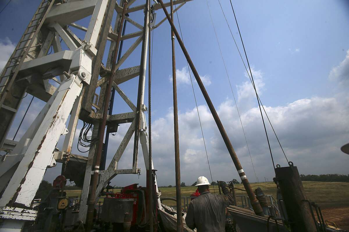 Roughneck Eluid Cervantes pulls up a section of drilling pipe with the help of machinery Thursday May 11, 2017 at the Abraxus Petroleum Shut Eye Unit oil drilling rig in the Eagle Ford Shale in Atascosa County, Texas.