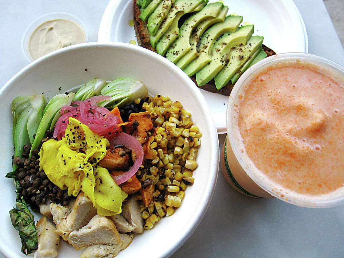The Good Kind also is known for dishes like its market bowl with black rice, vegetables and chicken, left, avocado toast and an Orange Creamsicle smoothie.