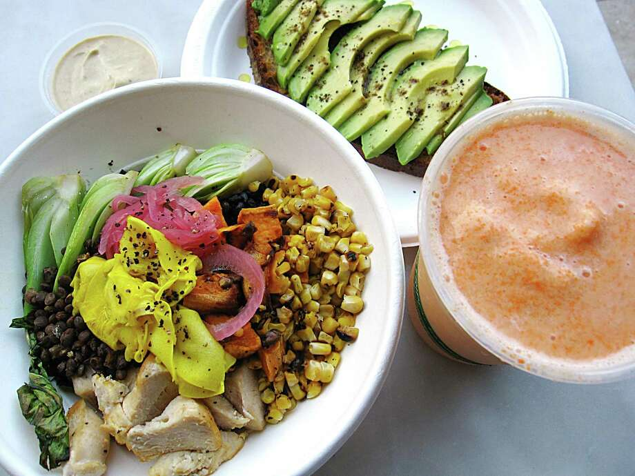 Market bowl with black rice, vegetables and chicken, left, avocado toast and an Orange Creamsicle smoothie from The Good Kind at The Bottling Department food hall at The Pearl. Photo: Mike Sutter /San Antonio Express-News