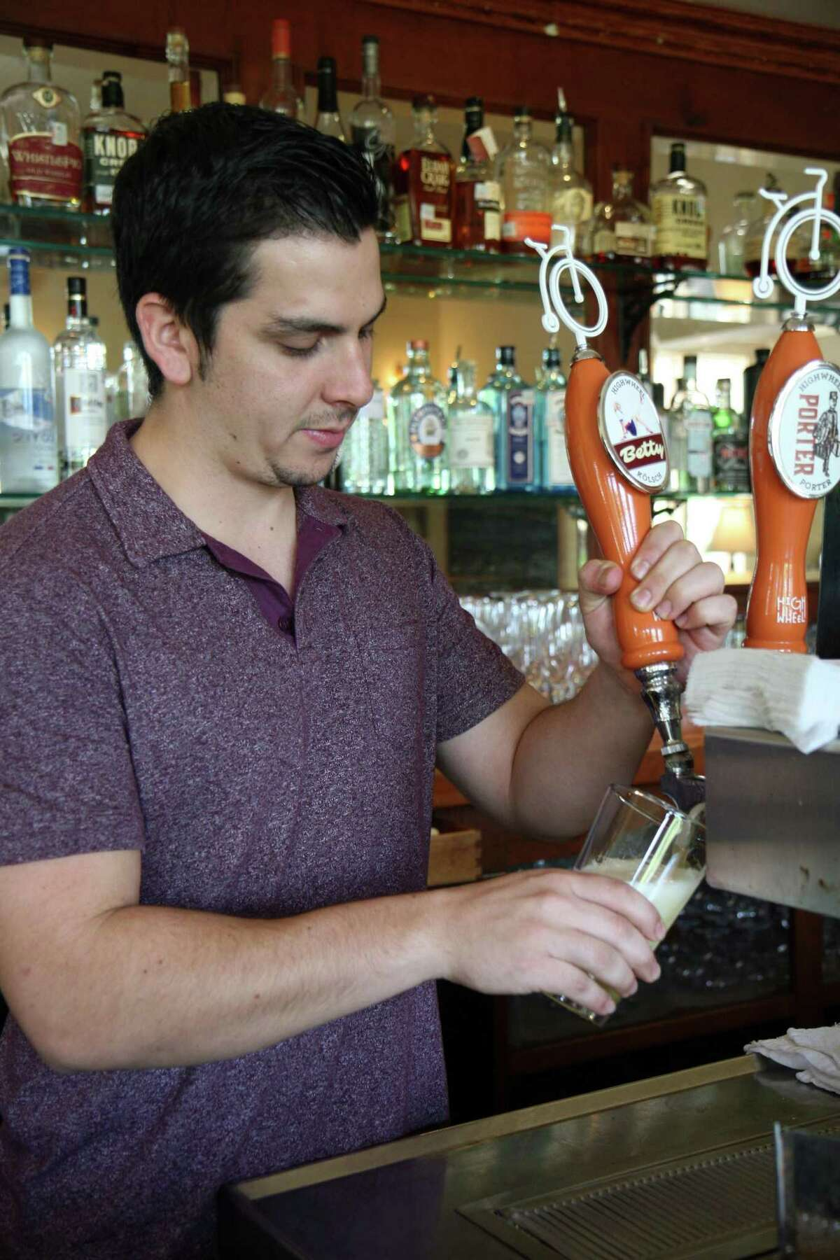 Liberty Bar bartender Jacob Herrera pours a pint of a Highwheel Beerworks beer. Small breweries like Highwheel that distribute to only a small, local audience are the fastest-growing segment of the craft beer industry.