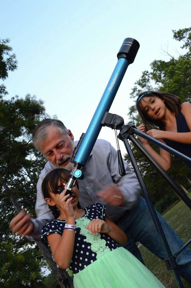Mark Dam of Darien helps his granddaughter, Maya Dam, 6, of Westport, look at the moon through his telescope, as her sister Emma, 9, looks on at the Recreation Department's last Waveny Concert of the season on Aug. 30 at Waveny Park in New Canaan. Photo: Jarret Liotta / For Hearst Connecticut Media / New Canaan News Freelance