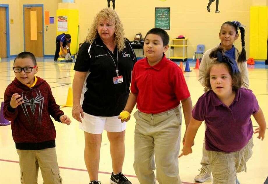 "LISD Adaptive PE Coach Olga ""Gogi"" Gutierrez works with her Special Education students at J.C. Martin Elementary School. Photo: Courtesy"