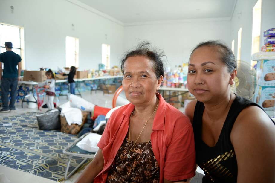 In Cambodian custom, the grown children look after their parents; Moonsun So (right) and her mother, Sort Tith, help in the only building in the community's spiritual center that was not gutted by Harvey. Photo: Y.C. Orozco/Houston Chronicle