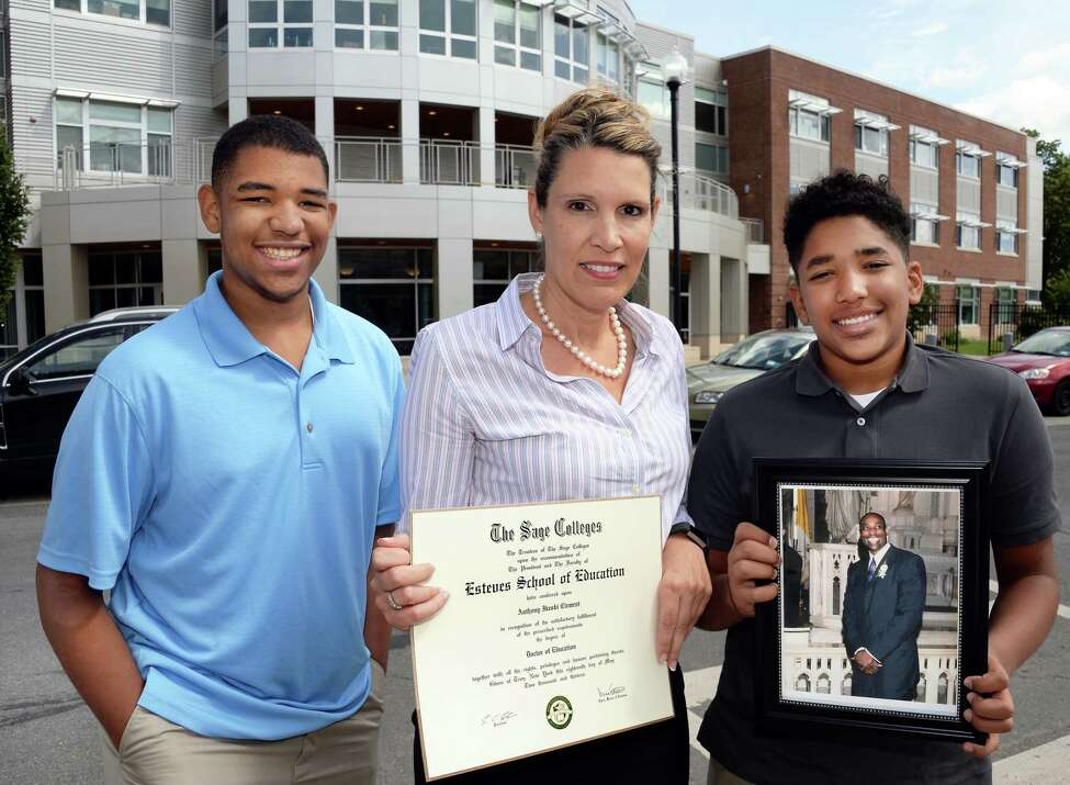 Jennifer Clement walks with sons David, 12, left, and Anthony, 14, hold a photo of her late husband high school principal Tony Clement and his posthumously awarded Doctor of Education degree at the the Tony Clement Center for Education, Friday Sept. 1, 2017 in Albany, NY. (John Carl D'Annibale / Times Union)
