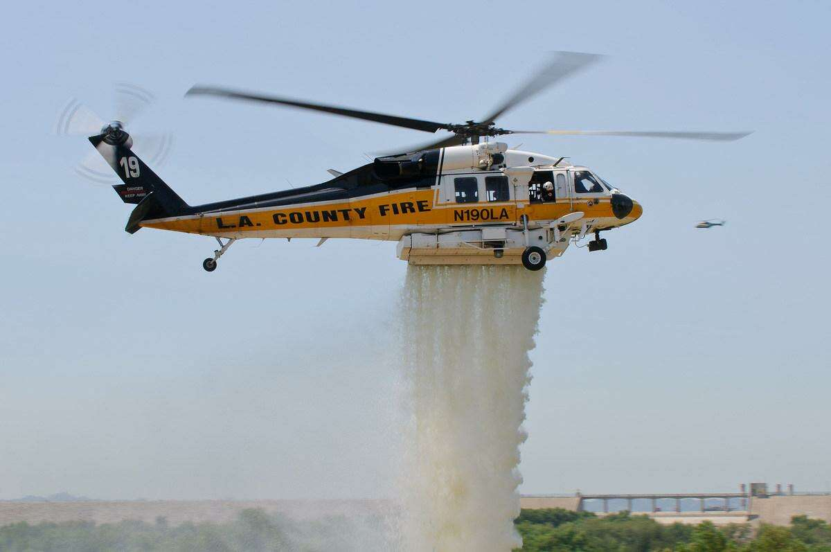 A L.A. County Sikorsky S-70 Firehawk helicopter demonstrates water suppression during a 2013 airshow.