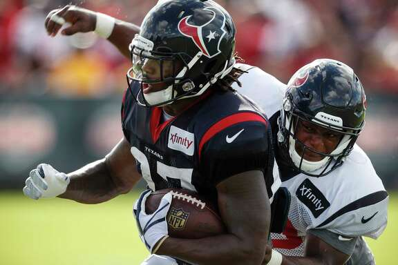 Houston Texans running back D'Onta Foreman (27) is hit by linebacker Avery Williams after making a catch during training camp at The Methodist Training Center on Tuesday, Aug. 22, 2017, in Houston. ( Brett Coomer / Houston Chronicle )