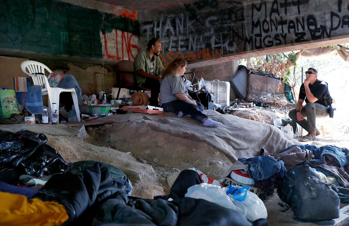 El Dorado County Deputy Blake Braafladt talks with Whitey and Sierra at their encampment under an abandoned highway 50 overpass on the outskirts of the city of in Placerville, Ca. on Tues. August 22, 2017. Braafladt is a member of the homeless outreach team.