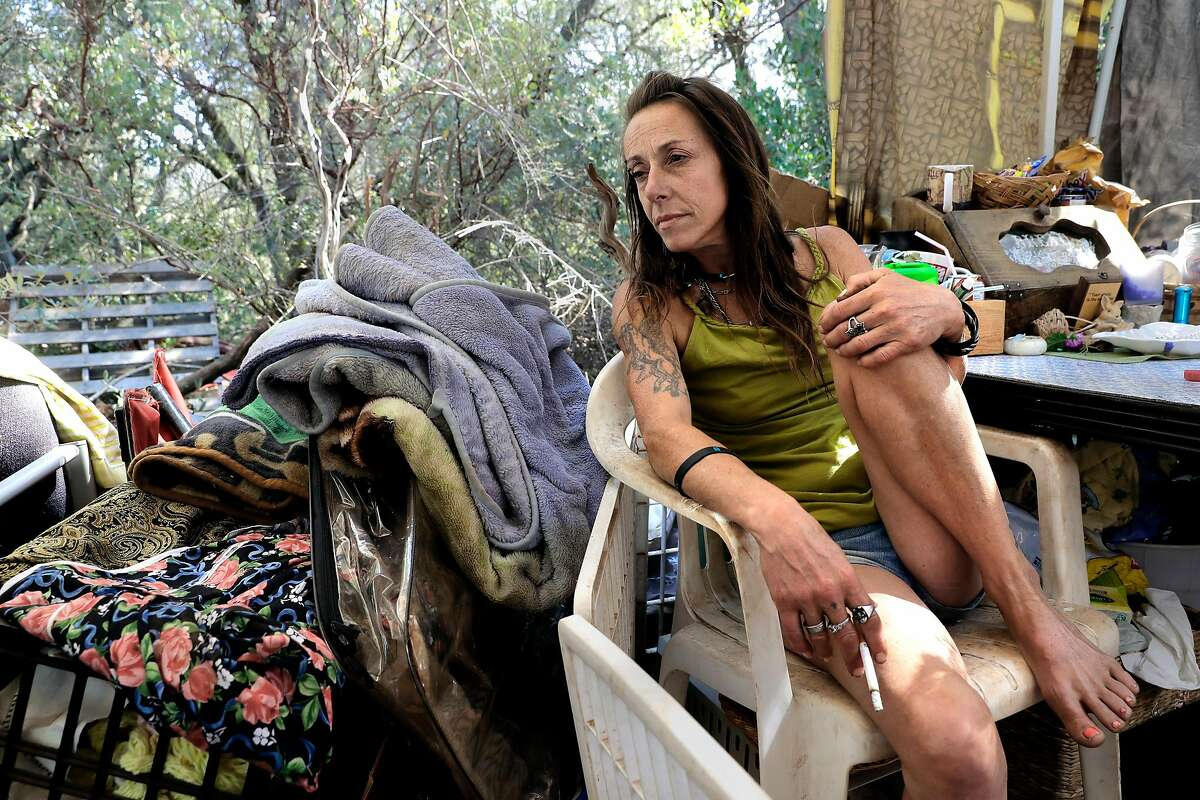 Billie Jo leans back at her homeless encampment near unincorporated Cameron Park in El Dorado County, which has seen its homeless population jump 122 percent since 2015.