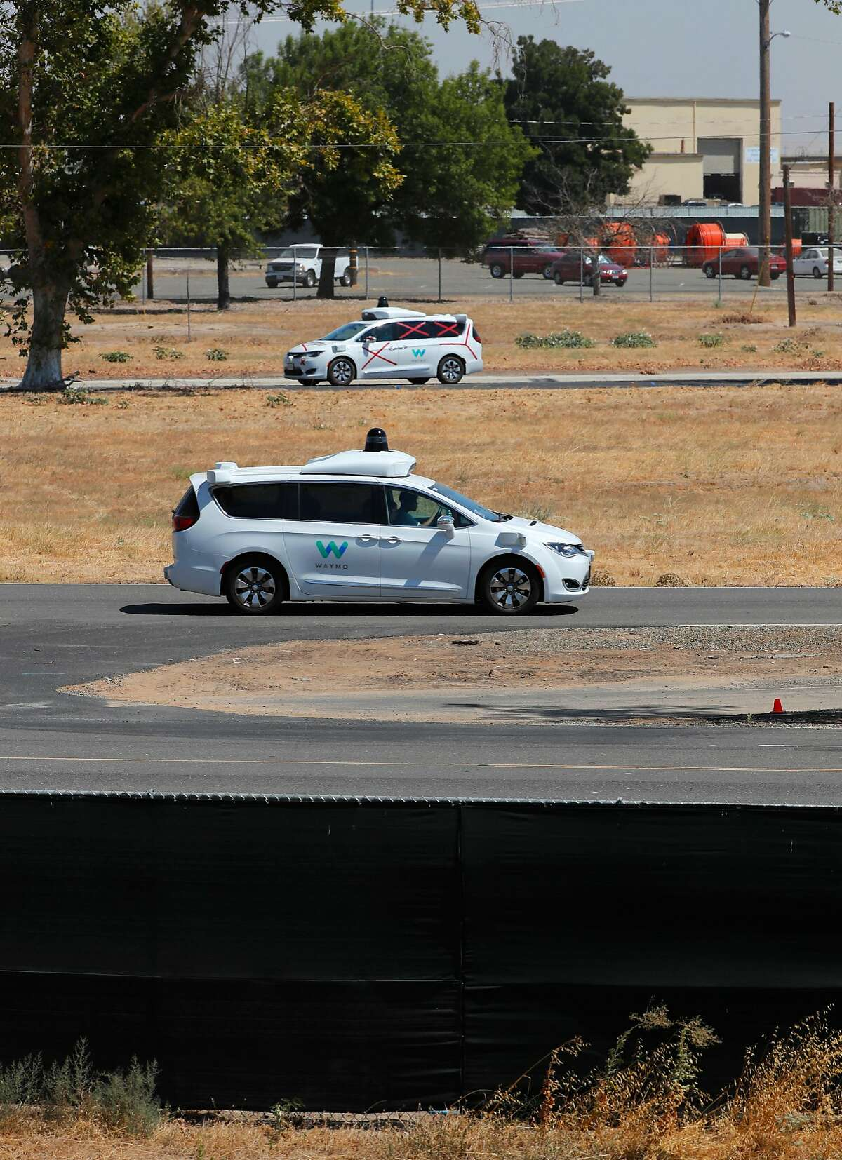 FILE-- Two Googgle Waymo autonomous vehicles navigate the roads inside their facility on the property of the now closed Castle Air Force Base, which is now a municipal airport in Atwater, Ca. on Thurs. August 31, 2017. A Waymo minivan on a test drive in Palo Alto was involved in a minor traffic accident in late August, with no injuries, according to a report the company filed with the state.