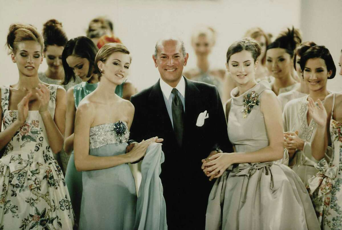 """""""The Glamour and Romance of Oscar de la Renta,"""" apresentation of nearly 70 extraordinary creations by the late fashion designer Oscar de la Renta, will be on view at Museum of Fine Arts, Houston Oct. 8-Jan. 28. This image shows the designer with models during the finale of his Spring 1996 fashion show."""