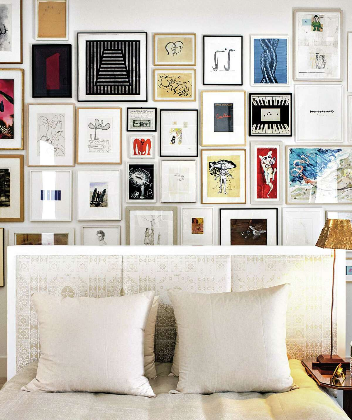 A salon-style art wall serves as a backdrop for the custom floating bed with a headboard upholstered in Casablanca silk by Rubelli.
