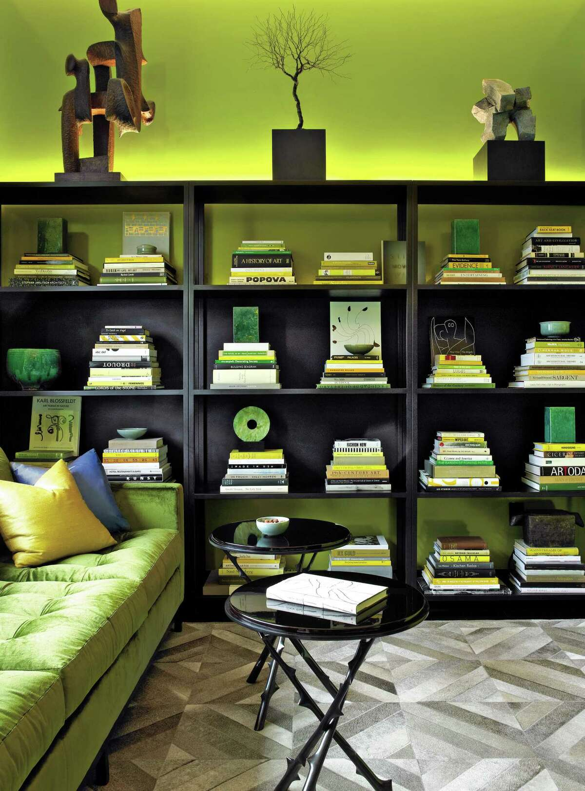 Acid-green lacquer walls and LED uplighting add a jolt of color to this den. A three-quarter-height bookshelf allows for the display of sculpture on top. The pieces here are from Maison Gerard.