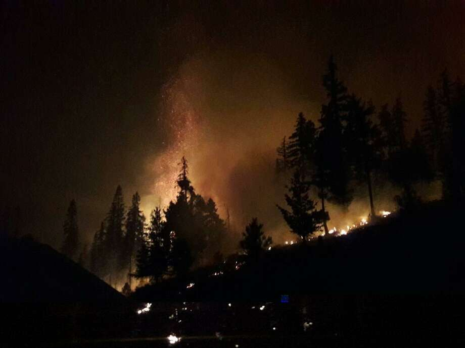 Flames amid trees are seen at the Jolly Mountain fire near Cle Elum. The fire had grown to more than 26,000 acres Thursday, with 5 percent of it contained. Photo: Pacific Northwest Team 2/InciWeb