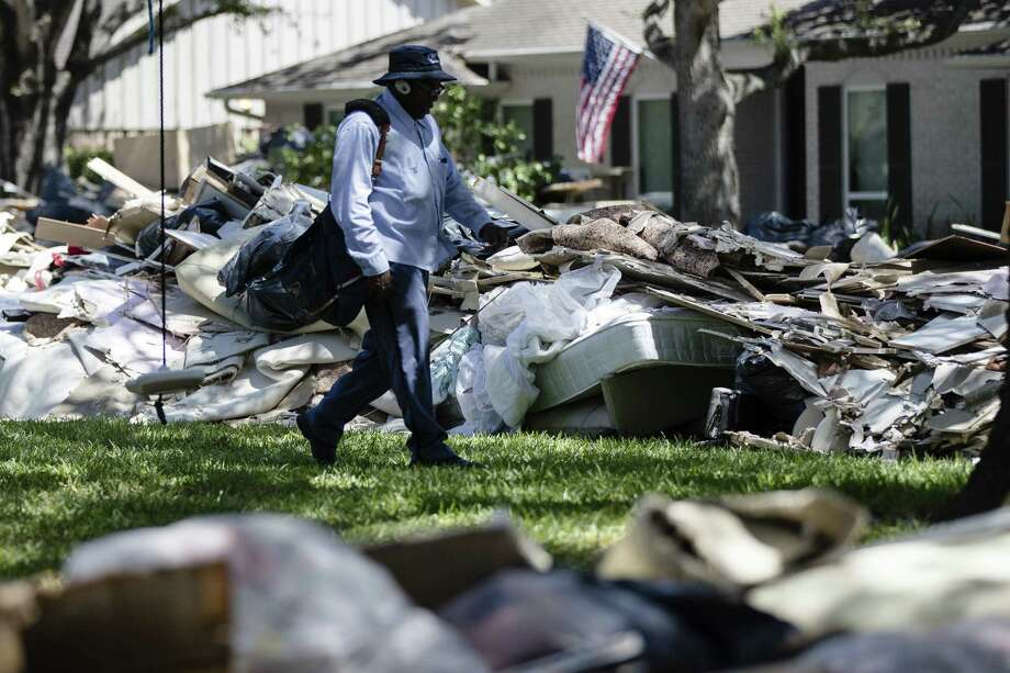 Postal worker Lonzell Rector makes his rounds among flood damaged debris from homes that lines the street in the aftermath of Hurricane Harvey on Thursday, Sept. 7, 2017, in Houston. Greenwich residents will hold a tag and bake sale Saturday, 9 a.m.-1 p.m., at 15 Owenoke Way to raise funds for Harvey relief. Photo: Matt Rourke / Associated Press / Copyright 2017 The Associated Press. All rights reserved.