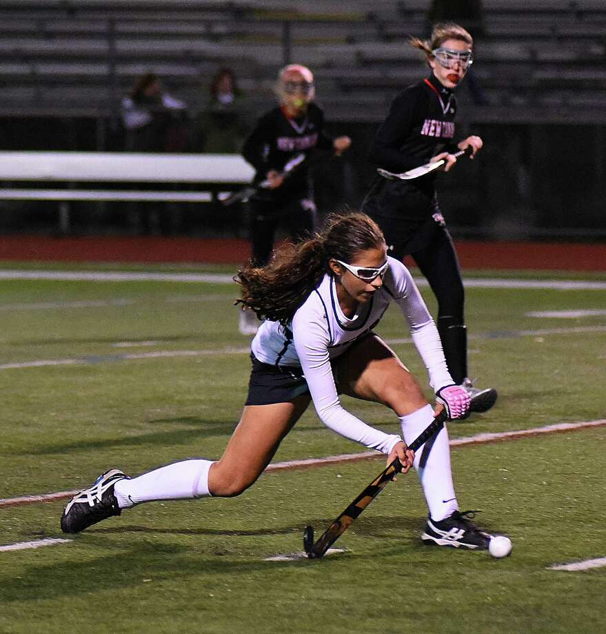 Norwalk's Jacqueline Mirabile, bottom, looks to push the ball into the circle as a pair of New Canaan defenders look on during the second half of Friday night's FCIAC field hockey quarterfinals at Testa Field in Norwalk. The host Bears won the game, 2-1. Photo: John Nash / Hearst Connecticut Media / Norwalk Hour