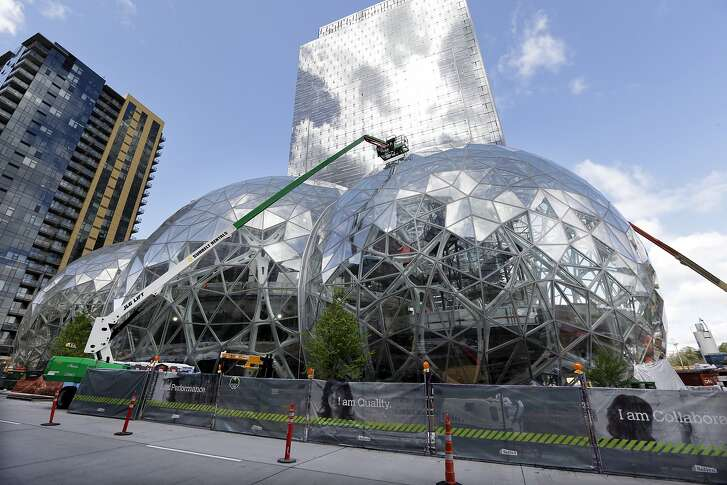 """FILE - In this April 27, 2017 file photo, construction continues on three large, glass-covered domes as part of an expansion of the Amazon.com campus in downtown Seattle. Amazon said Thursday, Sept. 7,  that it will spend more than $5 billion to build another headquarters in North America to house as many as 50,000 employees. It plans to stay in its sprawling Seattle headquarters and the new space will be """"a full equal"""" of its current home, said founder and CEO Jeff Bezos. (AP Photo/Elaine Thompson)"""