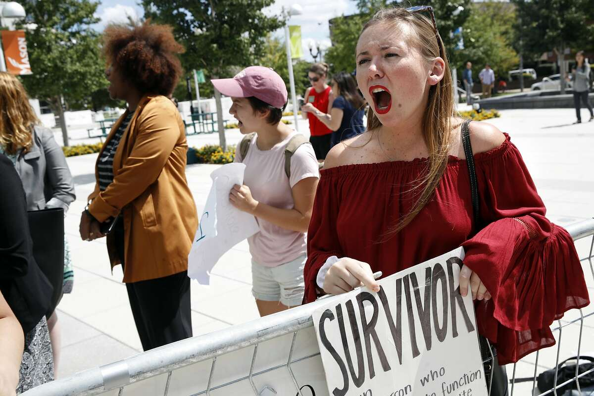 """Meghan Downey, 22, a recent graduate from the College of William & Mary, reacts outside an auditorium after Education Secretary Betsy DeVos spoke about proposed changes to Title IX, Thursday, Sept. 7, 2017, at George Mason University Arlington, Va., campus. """"It's pretty expected based on this administration,"""" says Downey, """"they don't condemn violence they perpetuate it."""" (AP Photo/Jacquelyn Martin)"""
