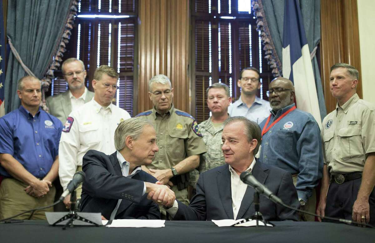 Gov. Greg Abbott, left, announces that Texas A&M University System Chancellor John Sharp, right, will head the Rebuild Texas initiative following Hurricane Harvey, Thursday, Sept. 7, 2017, at the Capitol in Austin, Texas. (Jay Janner/Austin American-Statesman via AP)