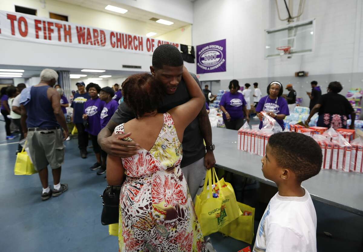 Andre Johnson hugs a woman as he handed out cleaning supplies and other items at the Fifth Ward Church of Christ, Thursday, Sept. 7, 2017, in Houston, where the Houston Museum of Natural Science teamed with The Andre Johnson Foundation, to bring interactive science education to families that have experienced lost. The museum outreach team brought a selection of living insects and other arthropods from the Cockrell Butterfly Center to give those in the Fifth Ward a short reprieve from Harvey. The Andre Johnson Foundation provided a hot meal and handed out cleaning supplies and toiletries for those in need of assistance. ( Karen Warren / Houston Chronicle )