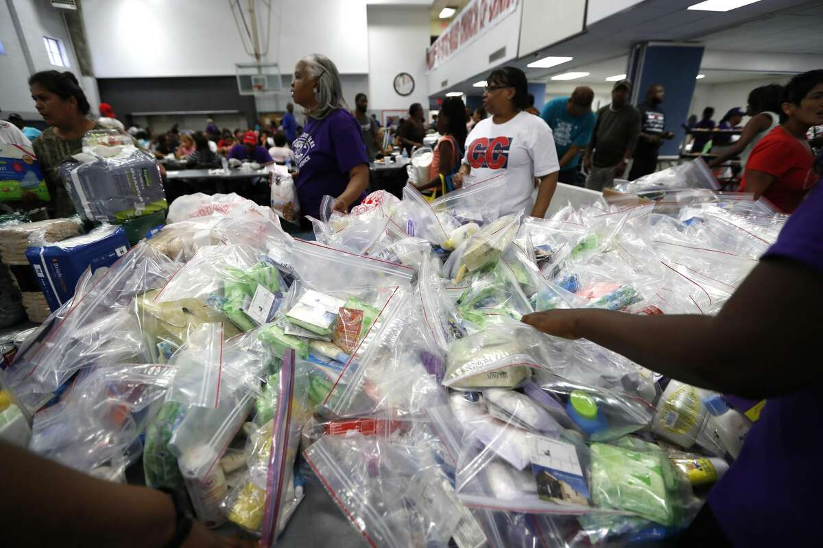 Fifth Ward Church of Christ volunteers hand out care packages at the church, Thursday, Sept. 7, 2017, in Houston, where the Houston Museum of Natural Science teamed with The Andre Johnson Foundation, to bring interactive science education to families that have experienced lost. The museum outreach team brought a selection of living insects and other arthropods from the Cockrell Butterfly Center to give those in the Fifth Ward a short reprieve from Harvey. Former Houston Texans Player Andre Johnson provided a hot meal and handed out cleaning supplies and toiletries for those in need of assistance. ( Karen Warren / Houston Chronicle )