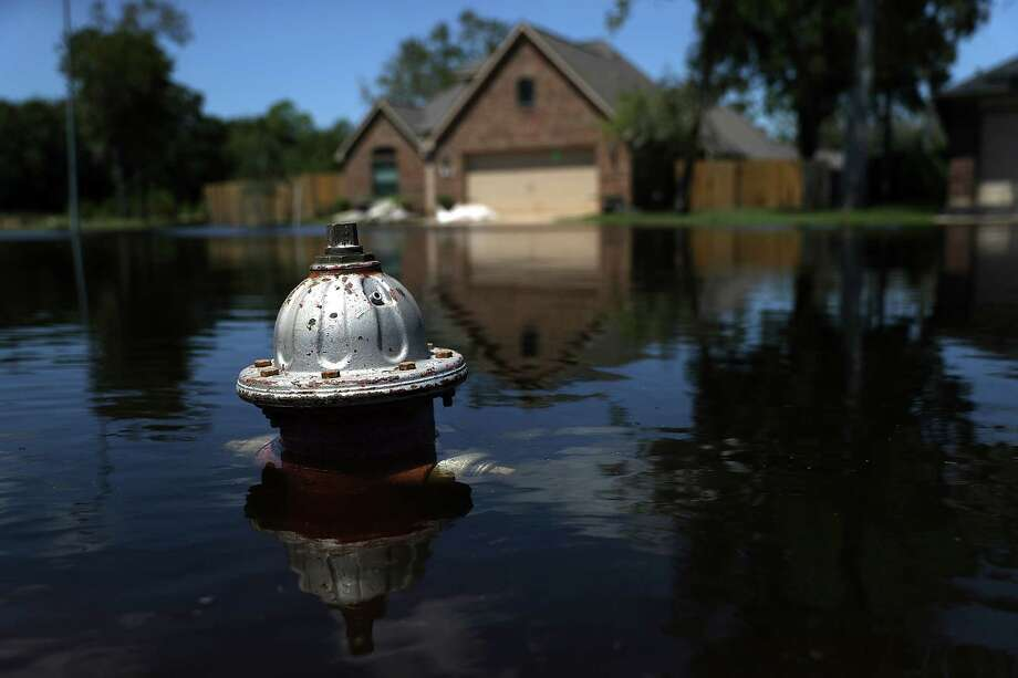 The top of a fire hydrant sticks out of floodwaters in front of a home on  in Richwood in Brazoria County more than a week after Hurricane Harvey hit  Texas. (Photo by Justin Sullivan/Getty Images) Photo: Justin Sullivan, Staff / 2017 Getty Images