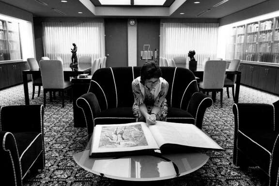 """A visitor at the P.I. Nixon Medical Historical Library looks over a book entitled """"Tables of the Skeleton and Muscles of the Human Body"""" by Bernhard Siegfried Albinus. It was published in 1749."""