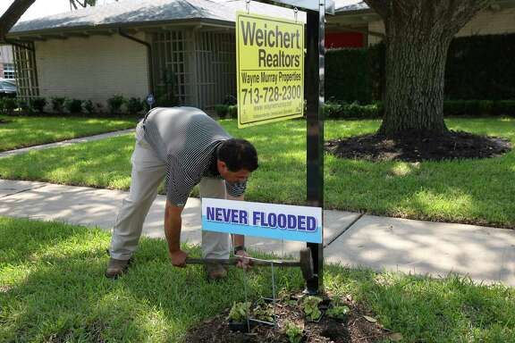 "Real estate agent Aaron Cruz puts a ""Never Flooded"" sign on the lawn of a Meyerland home. It's been listed at $579,000."