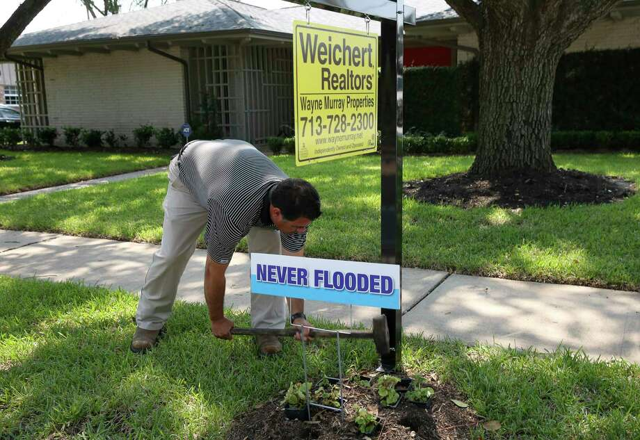 """Real estate agent Aaron Cruz poses for a photograph with a house on his listing in Meyerland Wednesday, Sept. 6, 2017, in Houston. This house was one of the few listings that didn't take on water in the area and Cruz put a """"Never Flooded"""" sign on the lawn after Tropical Storm Havery. ( Yi-Chin Lee / Houston Chronicle ) Photo: Yi-Chin Lee, Staff / © 2017  Houston Chronicle"""