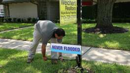"""Real estate agent Aaron Cruz puts a """"Never Flooded"""" sign on the lawn of a Meyerland home. It's been listed at $579,000."""