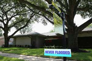 """Real estate agent Aaron Cruz put up a """"Never Flooded"""" sign on the lawn of a house that did not take on water in Meyerland after Tropical Storm Harvey flooded this area Wednesday, Sept. 6, 2017, in Houston. ( Yi-Chin Lee / Houston Chronicle )"""