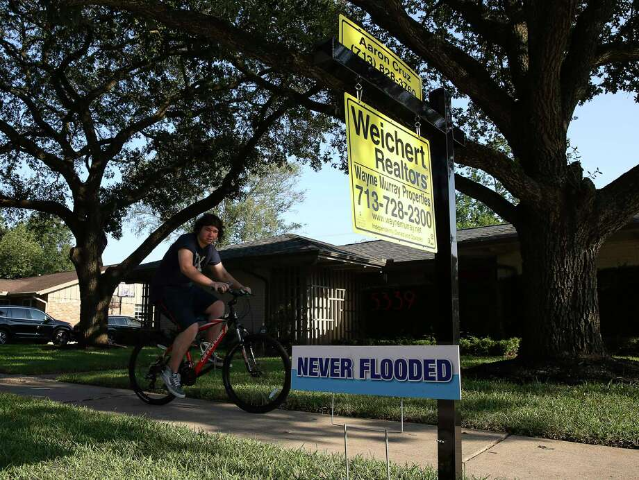 """Real estate agent Aaron Cruz put up a """"Never Flooded"""" sign on the lawn of a house that did not take on water in Meyerland after Tropical Storm Harvey flooded this area Wednesday, Sept. 6, 2017, in Houston. ( Yi-Chin Lee / Houston Chronicle ) Photo: Yi-Chin Lee, Staff / © 2017  Houston Chronicle"""