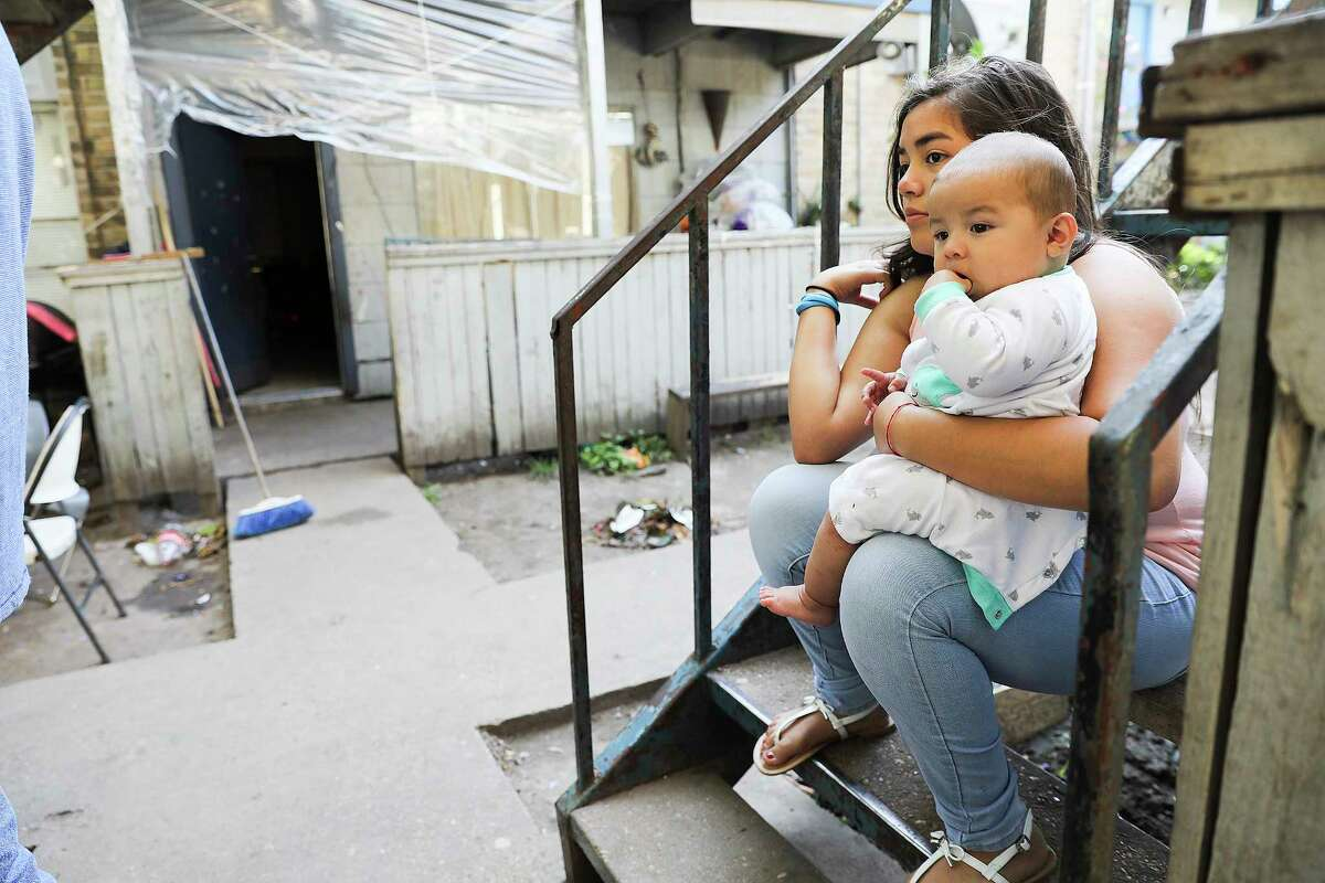 Stephanie Plancarte, 11, holds her five-month-old brother, Alexander Diaz, outside her Rockport Apartment that was damaged during Tropical Storm Harvey on Thursday, Sept. 7, 2017, in Houston. Many residents had to pay September's rent, even as their apartments are unlivable.