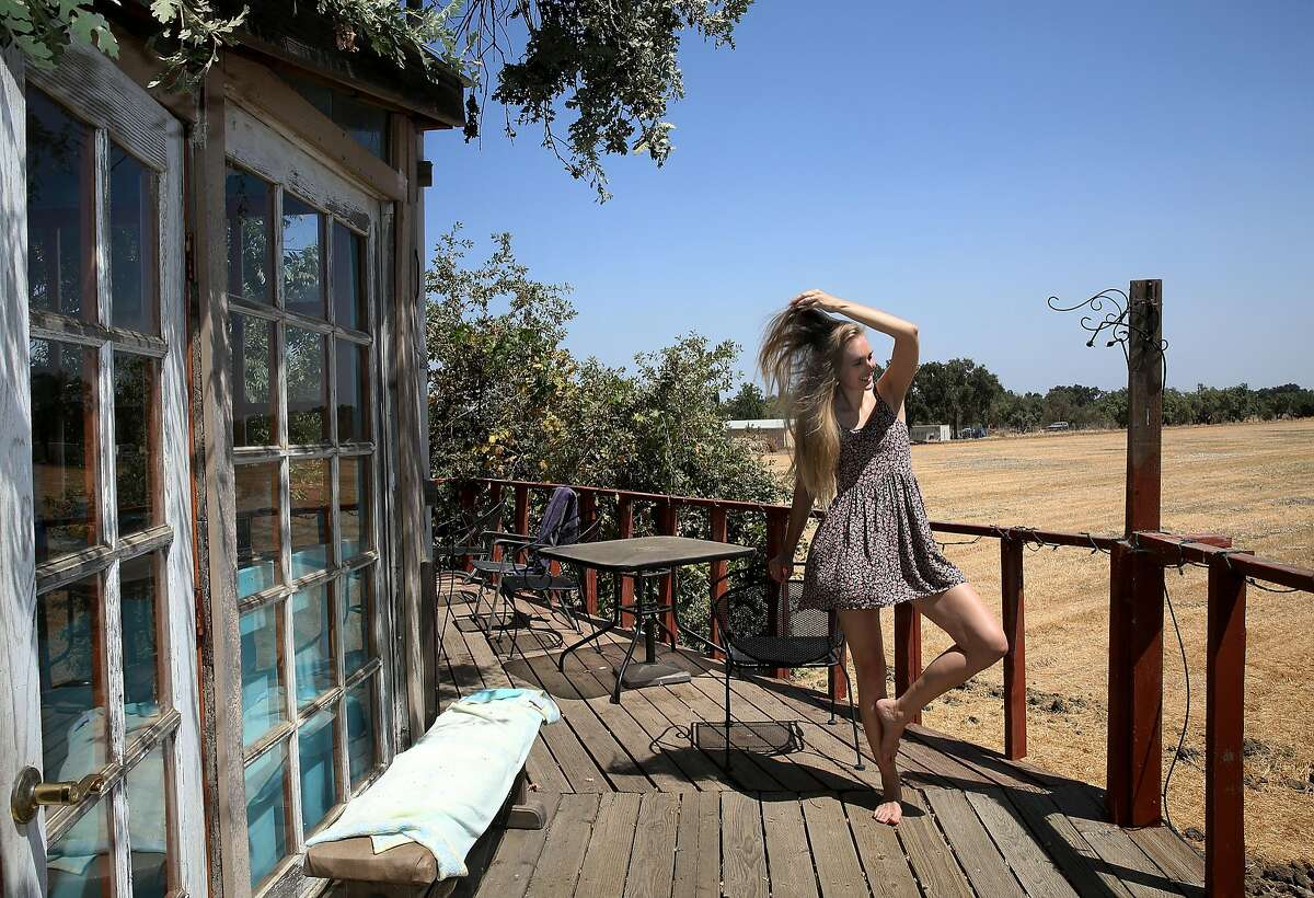 Artist Loie Hollowell shows the deck to a home she helped build and lived in for two years on Tuesday, August 15, 2017, in Woodland, Calif. She mentions the light on the farm fields was inspirational in her art.