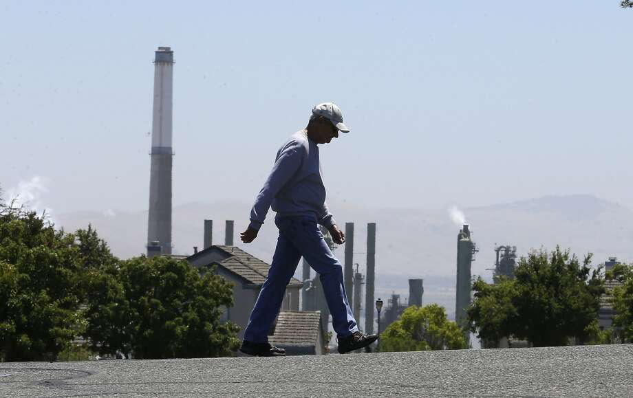 The stacks from the Valero refinery in Benicia are seen as a pedestrian walks in a nearby neighborhood. Photo: Rich Pedroncelli, Associated Press
