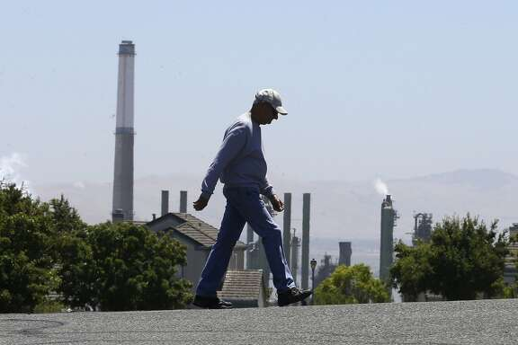 """File- In this July 12, 2017 file photo the stacks from the Valero Benicia Refinery are seen as a pedestrian walks in a nearby neighborhood, in Benicia, Calif. Gov. Jerry Brown and state lawmakers got national attention last month for extending the state's """"cap and trade"""" climate change law that keeps alive a program that raises hundreds of millions of dollars a year by auctioning off permits to release climate-changing gases.  California lawmakers return Monday, Aug. 21 , from a monthlong break with a busy agenda that includes tackling the state's housing crisis and deciding whether to make California a statewide sanctuary for people living illegally in the U.S. (AP Photo/Rich Pedroncelli, file)"""