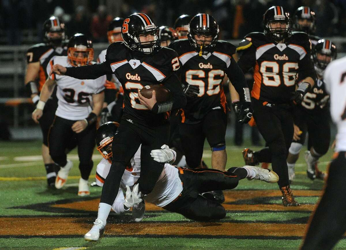 Shelton quarterback David Wells is tripped up by Ridgefield defender Jackson Mitchell during the first half of the Class LL football semifinals at Shelton High School in Shelton, Conn. on Monday, December 5, 2016.