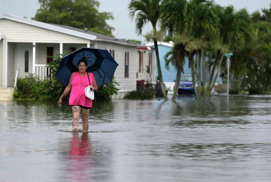 This June 7, 2017 file photo shows Peggy Wallace walking near her flooded neighborhood in Davie, Fla. With Hurricane Irma bearing down on Florida, an Associated Press analysis shows that the number of federal flood insurance policies written in the state has fallen by 15 percent. (AP Photo/Lynne Sladky, File) Photo: Lynne Sladky, STF / Copyright 2017 The Associated Press. All rights reserved.