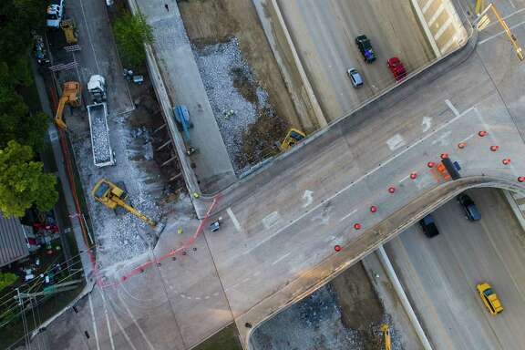 As traffic passes in the northbound lanes, work continues on a sinkhole along the southbound lanes of the the West Sam Houston Tollway  on Thursday.
