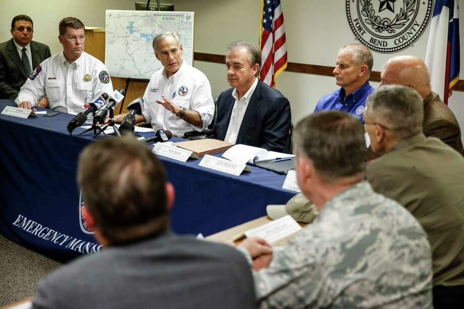 Gov. Greg Abbott, with Texas A&M Chancellor John Sharp (in jacket), outlines the Rebuild Texas efforts Thursday at a meeting with Fort Bend County mayors.