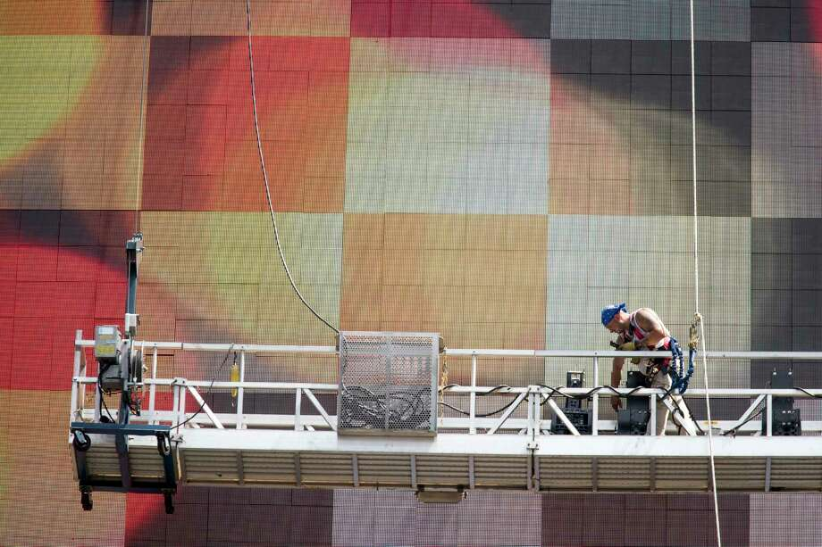 A worker on a scaffold does maintenance on the electronic Coca-Cola billboard in New York's Times Square. Worker productivity rose in the spring.  Photo: Mary Altaffer, STF / Copyright 2017 The Associated Press. All rights reserved.