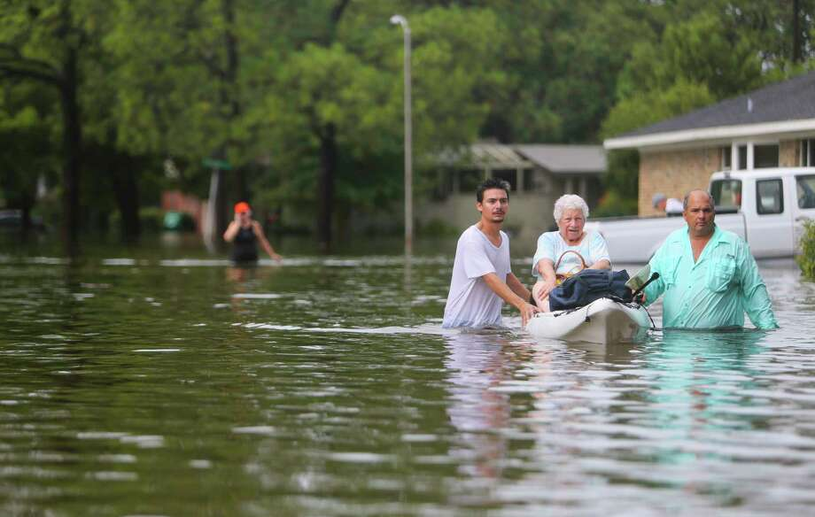FILE - A woman is rescued from her house during extreme flooding in Meyerland on Aug. 27, 2017, in Houston, Texas.  >> The following maps show a not-so-often-seen look at the effect Hurricane Harvey had on Houston Photo: Mark Mulligan, Staff Photographer / 2017 Mark Mulligan / Houston Chronicle