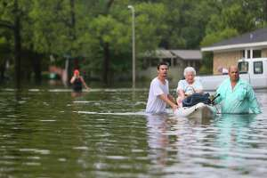 A woman is rescued from her house during extreme flooding in Meyerland, Sunday, Aug. 27, 2017, in Houston.  (Mark Mulligan / Houston Chronicle)