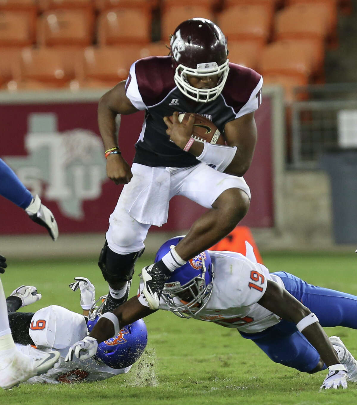 Texas Southern Tigers quarterback Jay Christophe (11) carries the ball and jumps over Houston Baptist Huskies players that are trying to tackle him during the third quarter of the game at BBVA Compass Stadium Thursday, Sept. 7, 2017, in Houston. ( Yi-Chin Lee / Houston Chronicle )