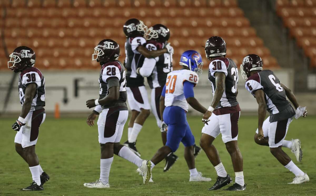 Houston Baptist Huskies running back LaDarius Dickens (20) walks away from the pack of Texas Southern Tigers players as the Tigers celebrate picking up a fumble ball from the Huskies during the second quarter of the game at BBVA Compass Stadium Thursday, Sept. 7, 2017, in Houston. ( Yi-Chin Lee / Houston Chronicle )
