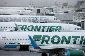 Frontier Airlines planes are in the foreground at Denver International Airport on April 4, 2017. (