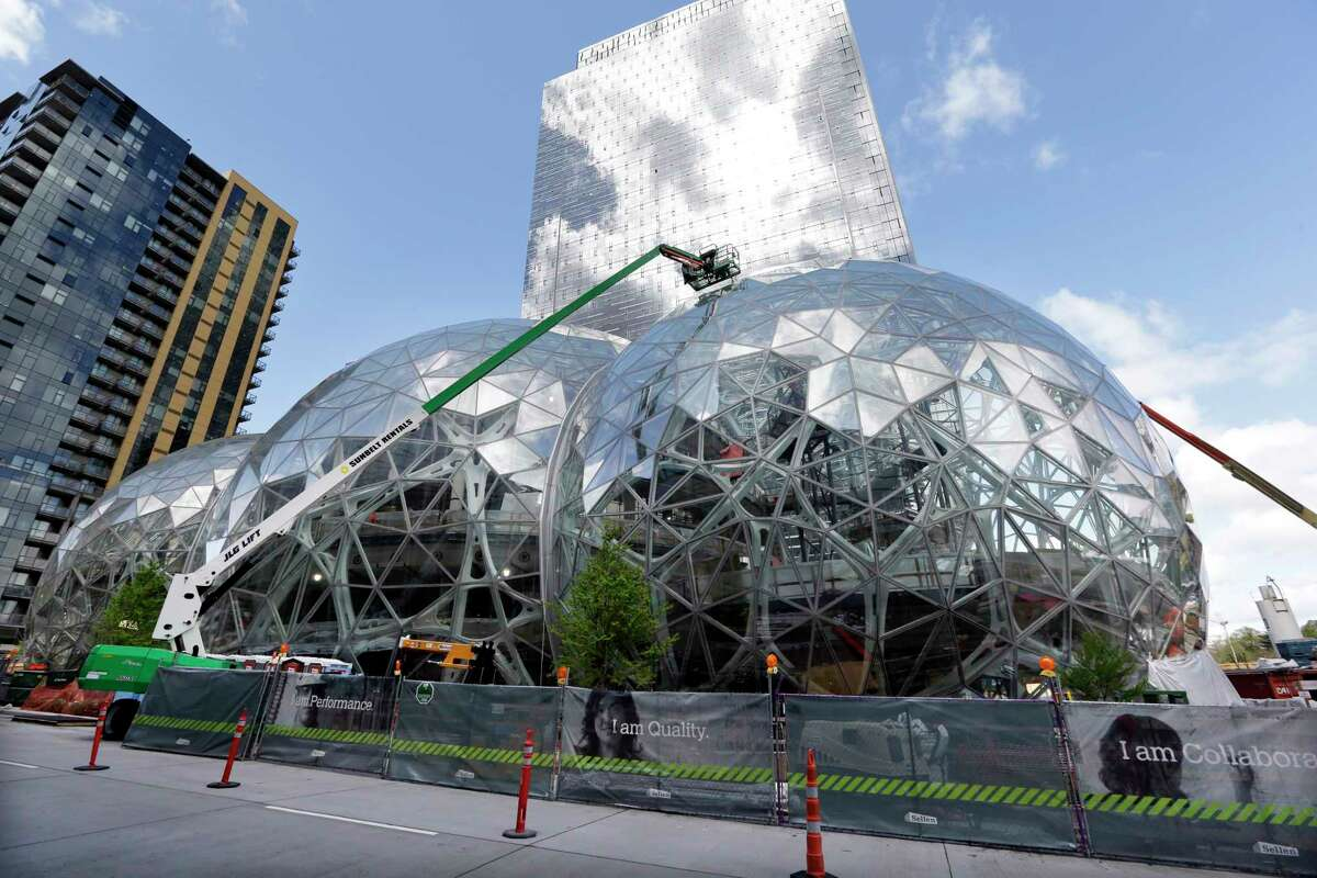 FILE - In this April 27, 2017 file photo, construction continues on three large, glass-covered domes as part of an expansion of the Amazon.com campus in downtown Seattle. Amazon said Thursday, Sept. 7, that it will spend more than $5 billion to build another headquarters in North America to house as many as 50,000 employees. It plans to stay in its sprawling Seattle headquarters and the new space will be