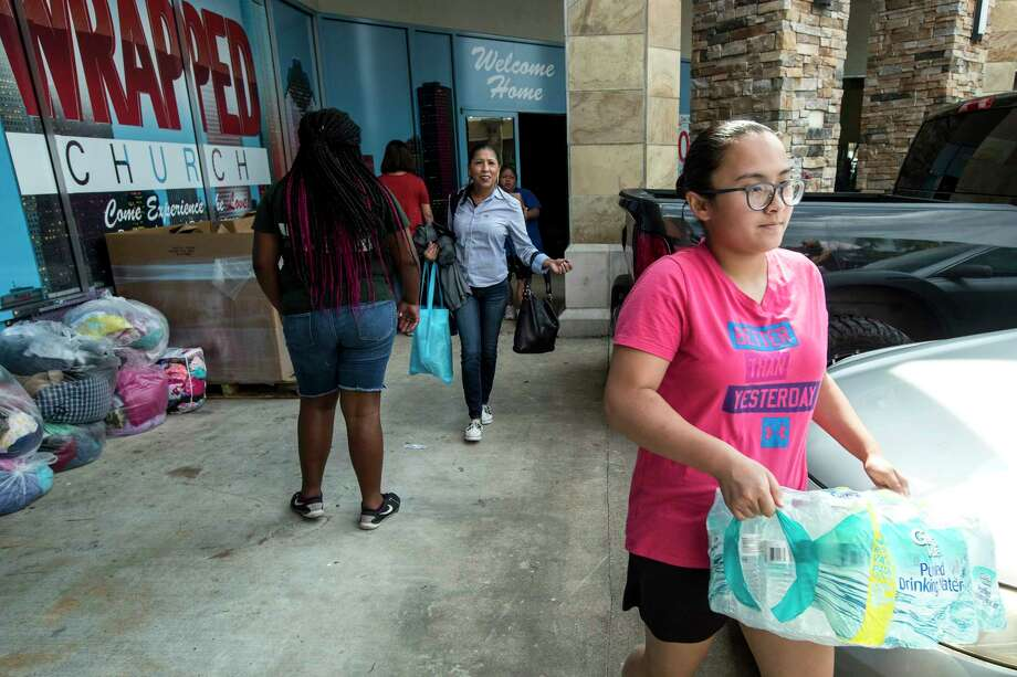 Mia Tran carries a case of water to be delivered to victims of Tropical Storm Harvey outside Get Wrapped Church on Tuesday, Sept. 5, 2017, in Spring. ( Brett Coomer / Houston Chronicle ) Photo: Brett Coomer, Staff / © 2017 Houston Chronicle
