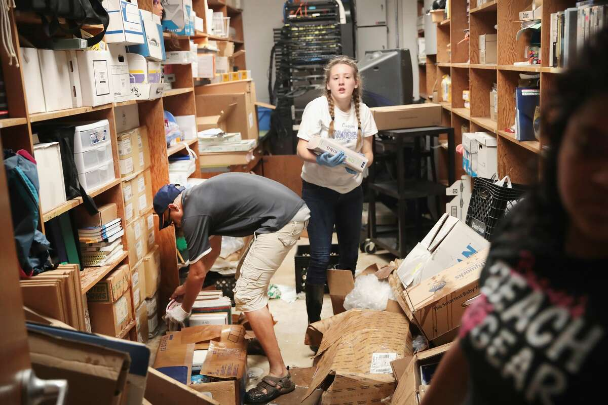 Volunteers and students from C.E. King High School help to clean up the school after torrential rains caused widespread flooding in the area during Hurricane on September 1.